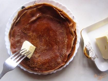 Нажарьте шоколадных блинов и каждый блин смажьте сливочным маслом.