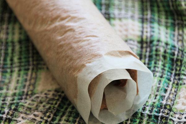 Горячий бисквит сверните плотным рулетом прямо вместе с бумагой. Помогайте себе полотенцем, чтобы не обжечься. Оставьте рулет остывать, а когда он будет тёплым уберите в холодильник.