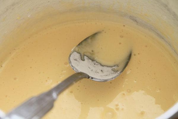 Тем временем приготовьте крем. Для этого желтки слегка взбейте миксером с ванильным сахаром и полной столовой ложкой крахмала. Крахмал лучше просеять, чтобы не было комочков.