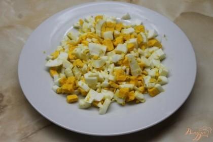 Яйца куриные отварить в крутую, почистить и нарезать мелким кубиком.