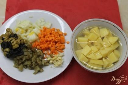 Нам надо сделать нарезку для солянки. И так картофель нарезаем средним кубиком, лук, чеснок, морковь и огурец маринованный нарезаем мелким кубиком, оливки и маслины нарезаем кольцами.