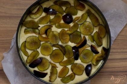 Тесто поместите в форму, дно которой застелено пергаментной бумагой, а бортики смазаны сливочным маслом. Сверху выложите кусочки слив.