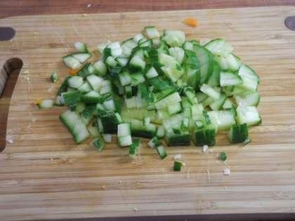 Свежий огурец вымыть, мелко порезать, добавить в салатницу