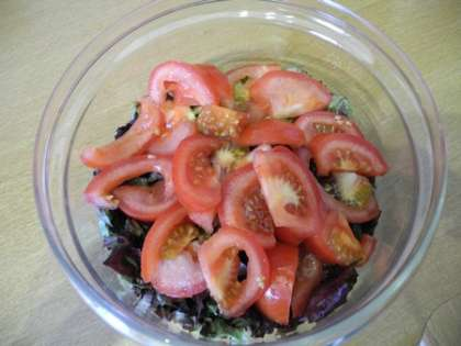 Помидоры нарезать дольками и сложить в салатницу