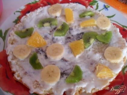 Корж смазываем кремом, выкладываем фрукты. Сверху выкладываем кусочки теста, опять фрукты, опять крем. И так формируем торт