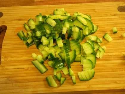 Огурец вымыть, мелко порезать и добавить в салатницу
