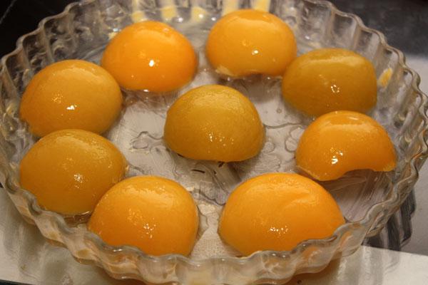 Плоскую форму для пирога смазываем маслом и раскладываем в ней кусочки персиков. Можно нарезать их мельче, а можно оставить половинками, как я.