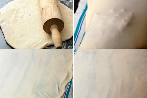 Рабочую поверхность посыпьте мукой и слегка раскатайте тесто с помощью скалки. Затем переложите тесто на большое чистое полотенце, тоже присыпанное мукой.  Просуньте руки под тесто ладонями вниз и аккуратно растягивайте до тех пор, пока оно не станет настолько тонким, чтобы через него был виден рисунок на ткани.  Старайтесь действовать быстро, чтобы тесто не успело высохнуть, но не порвите его.  Толстоватые края можно либо отрезать, либо растянуть их также тонко, как остальное тесто. Можно сделать это даже позже, уже после выкладывания начинки.
