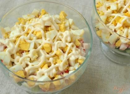 Поверх палочек выложить нарезанные кубиками яйца и смазать майонезом.