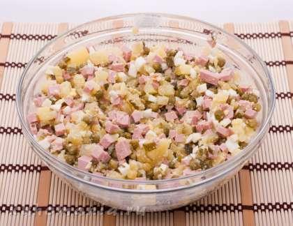 Нарезанные картофель, огурцы, яйца, колбасу выложить в емкость, добавить горошек, хорошо перемешать, смазать майонезом