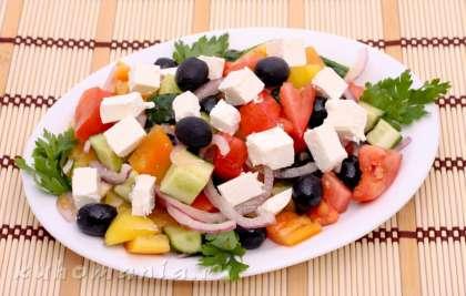 Выложить перемешанные овощи на блюдо, сверху выложить нарезанный сыр фета.