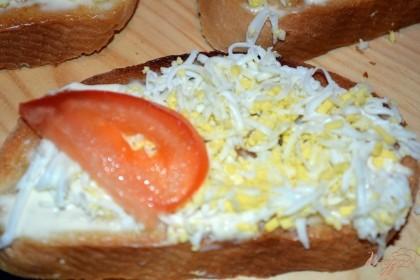 Помидор нарезать дольками. Выложите на каждый тост по 1-2 кусочка помидора. Присолите все. Поперчите.