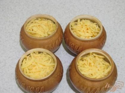 Твердый сыр натру на крупной терке. Посыпаю пшенную кашу в горшочках тертым сыром. Накрываю крышкой. Отправляю в горячую духовку на 10-15 минут при температуре 200 градусов до расплавления сыра.
