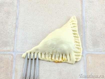 Завернуть в виде треугольного пирожка, придавить по краю вилкой. Если тесто прилипает, то обмакивать вилку в муку.