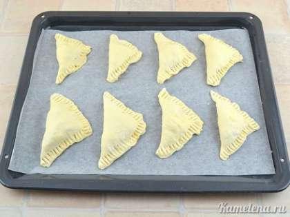 Положить заготовки на противень, застеленный пекарской бумагой. Поставить в разогретую до 180 градусов духовку. Выпекать примерно 30 минут.