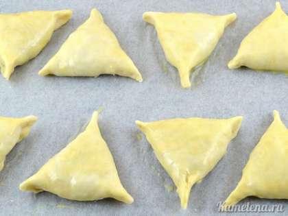 Полученные заготовки выложить на противень, застеленный пекарской бумагой. К желтку добавить ложку воды, взболтать. Смазать заготовки.