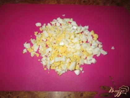 Отварим крутые яйца в течении 5 минут, охладим, почистим и нарежем кубиками.