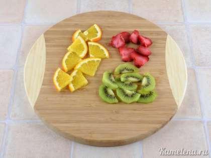 Подготовим фрукты. Апельсин порезать кружками, и каждый кружок на 4 части (по желанию, можно срезать кожуру). Киви почистить, порезать на половинки круга. Клубнику порезать пластинками.