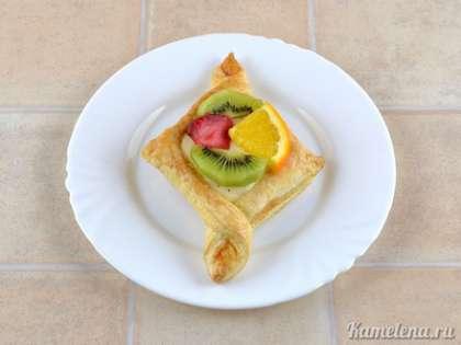 Сверху на крем выложить кусочки фруктов.