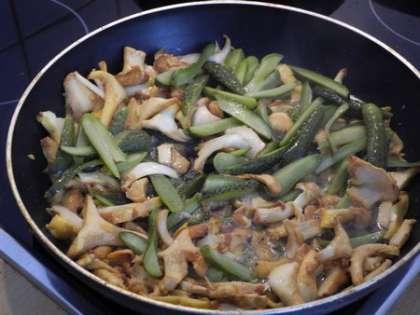 К грибам добавить соленые огурцы и потушить