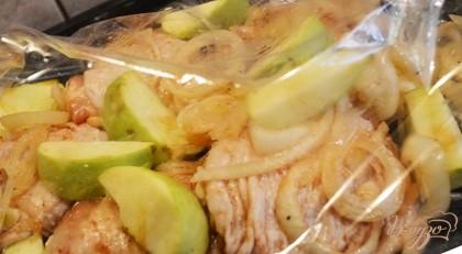 Промаринованное мясо еще раз перемешайте, выложите в рукав для запекания. Яблоки очистите от семян. Нарежьте дольками. Добавьте к мясу. Края рукава свяжите защипами. Уложите рукав на противень. Запекайте при 200 градусов около часа.