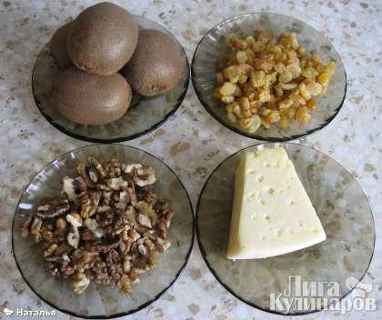 """Для салата """"Изумрудное кольцо"""" понадобятся: киви, орехи грецкие, сыр, чеснок,  изюм распаренный,  предварительно отваренная морковь, яйца, сваренные вкрутую, лук репчатый жареный, заправка."""