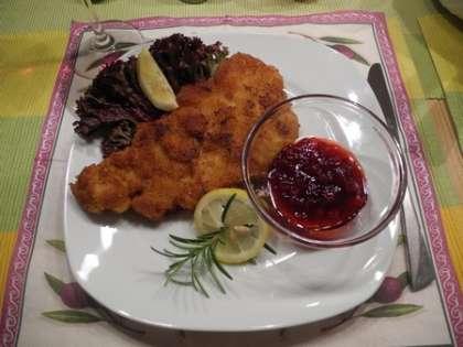 Готовые шницели выложить на тарелки, украсить лимоном, листьями салата и брусничным вареньем