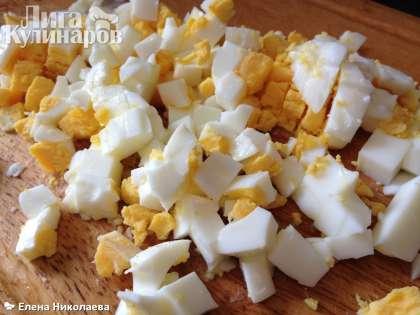 Яйца отвариваем вкрутую, охлаждаем, очищаем и режем кубиками. Добавляем к салату