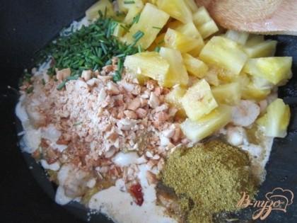 Вылить сливки, выложитькусочки ананаса,  орех, нарезанный мелко лук и специи.У меня имеется сбор из карри, кориандра, куркумы,мускатного ореха, имбиря, кардамона, красного перца и гвоздики. Ароматный, в меру пикантный и яркий по цвету.Перемешать, накрыть крышкой и довести до кипения.Затем на тихом огне потушить в течении 10 мин.