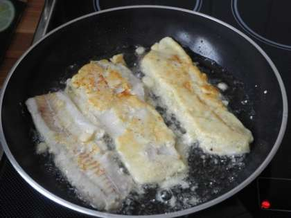 Перевернуть лопаточкой аккуратно рыбу и жарить еще на среднем огне 5 минут