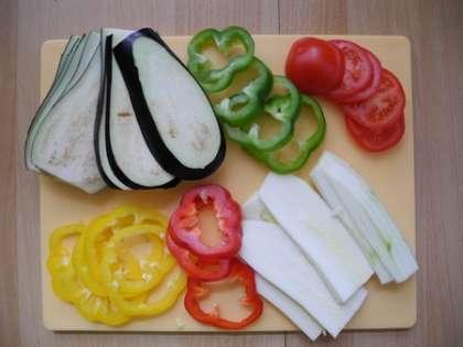 Нарезать баклажаны, перцы, кабачки и помидоры