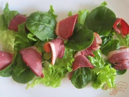 По тарелочкам разложить листья салата и кусочки грудки.