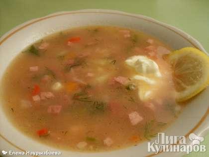 Разлить солянку с колбасой по тарелкам, положить в каждую кружок лимона и сметану.  Приятного аппетита!