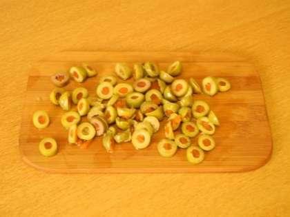Оливки порезать и выложить на тесто
