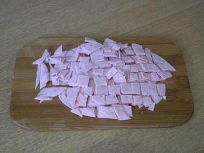 Колбасу мелко порезать и выложить на тесто