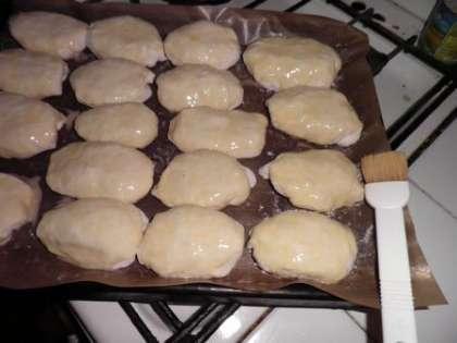Смазать пирожки сверху желтково-молочной смесью