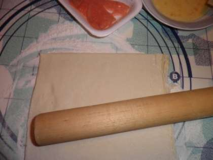 Тесто разморозить, посыпать рабочую поверхность мукой и раскатать тесто. Раскатанное тесто порезать на треугольнички