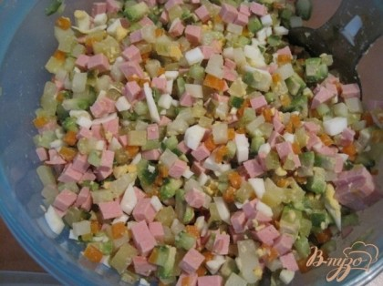 Нарезать огурцы кубиками. Нарезать каперсы, они дают пикантность салату. Добавить зеленый горошек и нарезанную колбасу, яйца. Колбасу лучше заменить куриным филе и это будет правильно. Аккуратно перемешать.