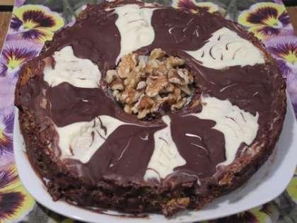 Украсить торт полосками из черного и белого шоколада, посыпать сверху орешками