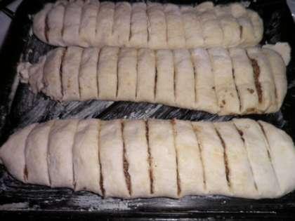 Свернуть (вдоль) в трубочку. Положить трубочки в ряд на смазанный маслом противень швом вниз. Разрезать трубочки сырыми на порционные кусочки.