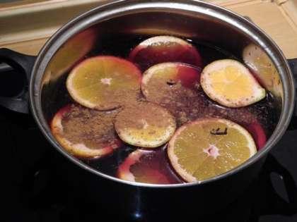 Апельсин и лимон порезать кружочками и добавить в кастрюлю. Положить корицу и гвоздику.