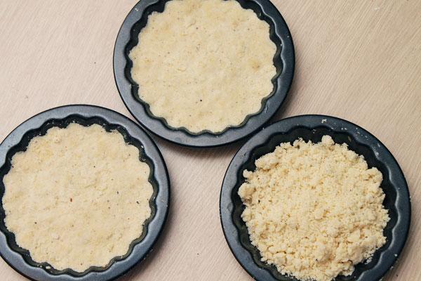 В формочки насыпайте крошку и утрамбовывайте, чтобы получился слой около 0,5 см. Формочки не должны быть влажными, иначе печенье прилипнет. Можно смазать их маслом. Наколите вилкой в двух-трёх местах и отправляйте в духовку в небольшой жар, 170 градусов, минут на 7-10. Печенье не должно стать коричневым, только немного подрумяниться.