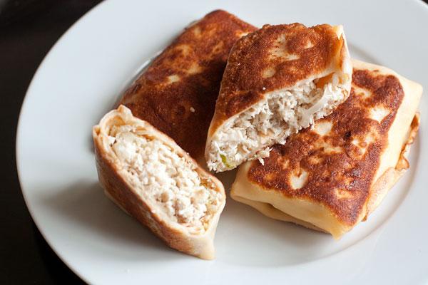 Завернутые блины обжарьте с обеих сторон, если перед этим вы их замораживали, то прикройте крышкой, чтобы начинка хорошо прогрелась.  Подавайте горячими или холодными со сметаной или сливочным соусом.