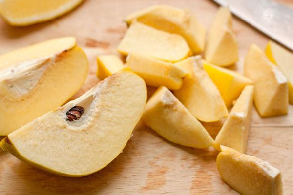 Разрежьте плоды на 4 части и удалите косточки, затем нарежьте дольками. Разрезайте фрукты поочередно, сразу сбрызгивая лимонным соком, т.к. на воздухе айва быстро темнеет.  Сложите нарезанную айву в кастрюлю, засыпьте сахаром и оставьте, прикрыв полотенцем, на сутки.