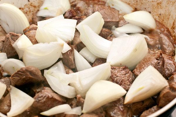 Очистите пару средних луковиц, разрежьте каждую на 6-8 долек и добавьте к мясу в сковороду. Готовьте все вместе 3-4 минуты.