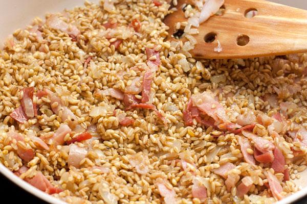 Всыпьте в сковороду стакан перловой крупы, помешайте, чтобы крупа покрылась маслом. Влейте вино и дайте ему выпариться на большом огне, посолите.  Теперь подливайте очень горячую воду (просто вскипятите чайник и держите его под рукой) небольшими порциямию Помешивайте и давайте жидкости впитаться каждый раз перед добавлением следующей порции.