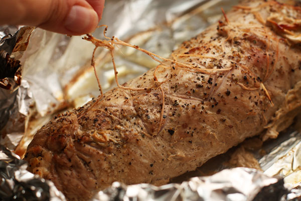Запекайте в разогретой до 180 градусов духовке, обернув фольгой, в течение 40 минут. Затем раскройте фольгу, увеличьте жар до 200 градусов и готовьте еще 20 минут, периодически поливая рулет образовавшимся соком.  Когда мясо будет готово, удалите нитки и зубочистки.