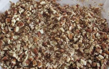 Подготовьте простой противень. На него нужно высыпать грецкие орехи и запекать в духовке (180°С) 10-15 мин. Периодически помешивайте орехи. Достаньте и остудите. После чего орехи самостоятельно измельчите в блендере.