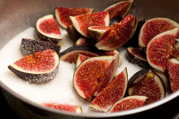 У инжира отрежьте жесткие хвостики и нарежьте плоды дольками. Сложите их в кастрюлю с сахаром.