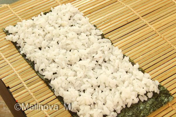Сборка суши: берем половинку нори (которая разрезана поперек перфорации) и выкладываем на нее рис тонким слоем, оставляя на правом краем полоску свободную от риса около 1 см.